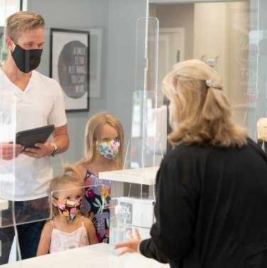 Family checking in at dental office front desk