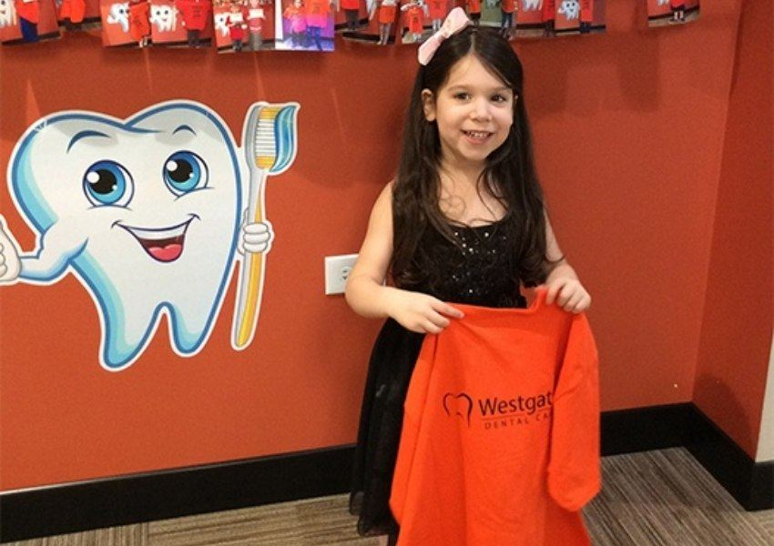 Little girl holding t-shirt for cavity free prize