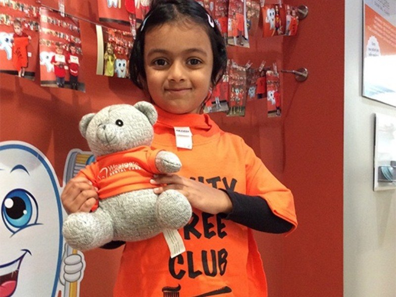 Little girl holding teddy bear cavity free club prize
