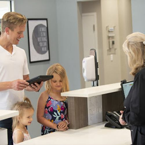 Father and his daughters checking in at dental office reception desk