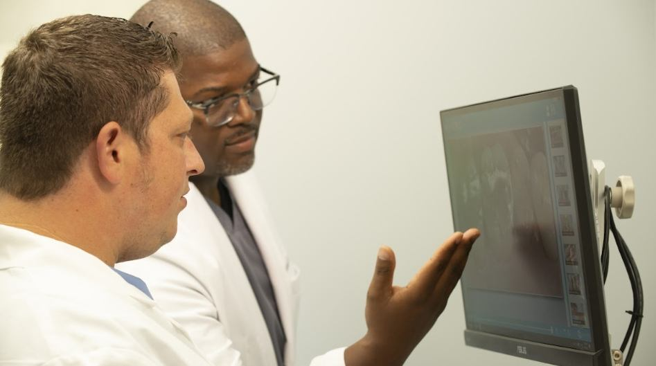 Doctor Christian and associate dentist reviewing dental x-rays