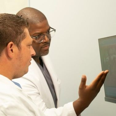 Two dentists looking at dental x-rays