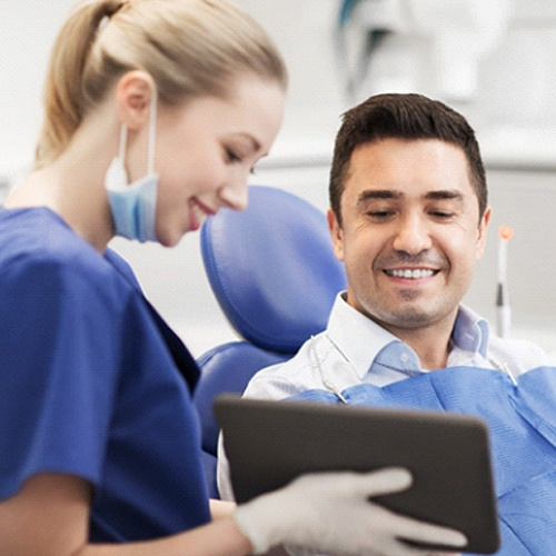 Woman giving thumbs up after dental implant retained denture placement