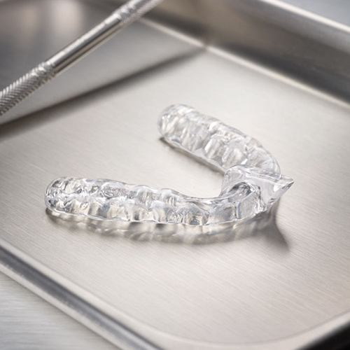 Clear mouthguard for sleep disorders on metal tray