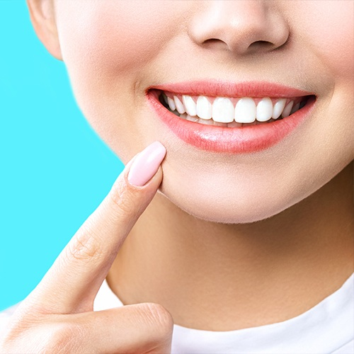 Woman pointing to smile after teeth whitening