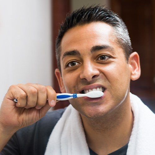 Man brushing his teeth after receiving a tooth colored filling