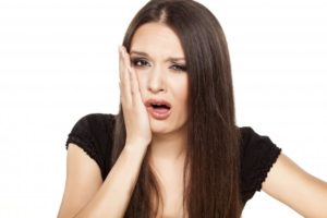 woman with dental pain, tooth pain, tooth sensitivity