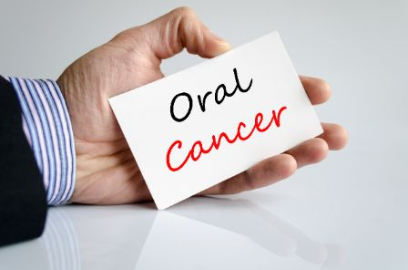"Someone holding a card that reads, ""Oral Cancer"""