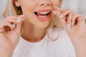 Close up of blonde woman using flossing tips