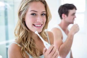 Woman brushing her teeth using tips from safe dentist
