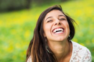 Woman smiling after seeing the dentist in Arlington Heights