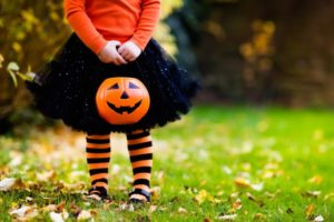 Little girl trick or treating while avoiding cavities after Halloween