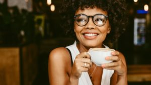 Woman smiling with coffee after brushing teeth before breakfast