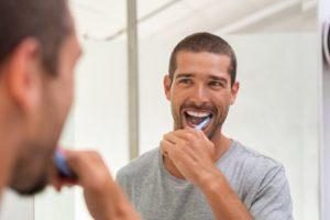 Man brushing his teeth using oral hygiene tips