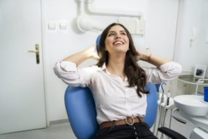 Woman who beat dental anxiety relaxing in dental chair