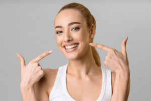 Woman smiling while pointing to her teeth